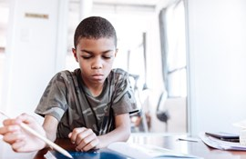 koncentreret elev. sort. elev. skole. klasserum. blyant. sidder ved bord. etnisk indlæring.